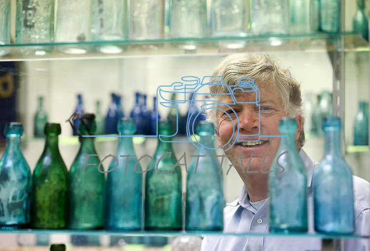 Author Fred Holabird poses with his extensive collection of antique drug store bottles that he's found around the state. Holabird, who just released his second volume of his The Nevada Bottle Book series, talks in his office in Reno, Nev. on Tuesday, Feb. 14, 2017. (Cathleen Allison/Las Vegas Review-Journal)