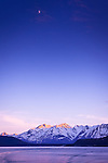 Alpenglow on Chilkat Mountains, crescent moon above the peaks, Inside Passage near Haines, SE Alaska in early summer.