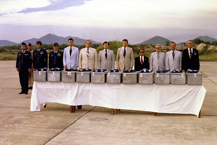 This picture was taken on August 27, 1978 at Noi Bai airport, Hanoi, Vietnam.  The group shown is a Congressional Delegation.led by Representative Sonny Montgomery, who was then Chairman of the Select Committee on POW/MIAs.  The event was the return of eleven sets of U.S. military service members remains (contained in the metal boxes each with a US Flag). The remains were transported that day from Hanoi by a US Military Honor Guard to Hickam AFB Hawaii for positive identification.  It was said at the time that this CODEL was the first to visit Hanoi after the end of the Vietnam War and the first return of US Military remains by Vietnam  In the picture, from right to left:.Representatives Sonny Montgomery, James Broyhill, George Daniels, Antonio Won Pat, John Murtha, Hensen Moore, Sam B. Hall, and Ike Skelton.  The military escorts  were Colonel Ted Reese (Lt. General, USAF Ret.) Major Douglas Roach (Colonel, USAF Ret.) and Senior Master Sergeant Peter Steffes (Chief Master Sergeant, USAF Ret.) The photo was taken by one of the press photographers with us on the trip, I think it was AP, but not sure and I do not have a name.  The original photo was given to Representative Montgomery who then gave a copy to the rest of the delegation.