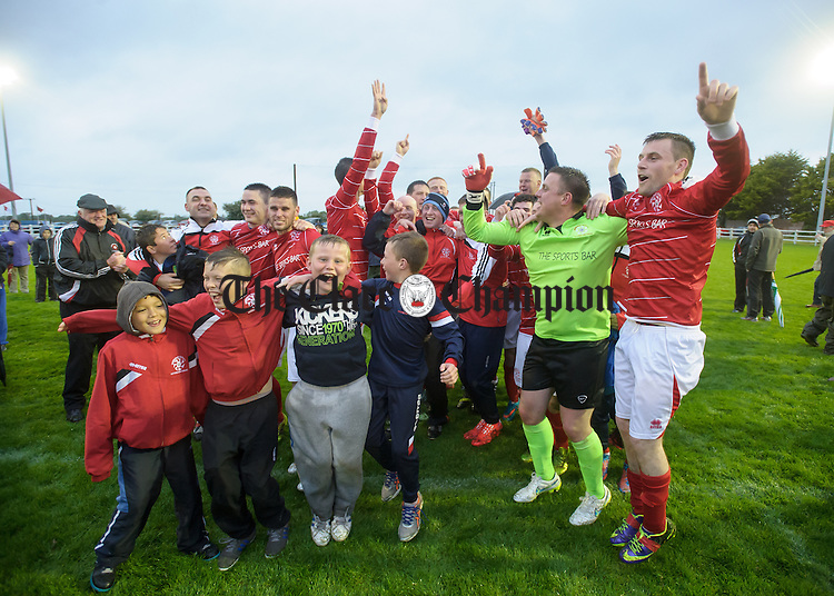 Newmarket Celtic players including hat trick goal scorer Davy Mc Carthy at right and young fans celebrate their win over Bridge United in the Cup final at Doora. Photograph by John Kelly.
