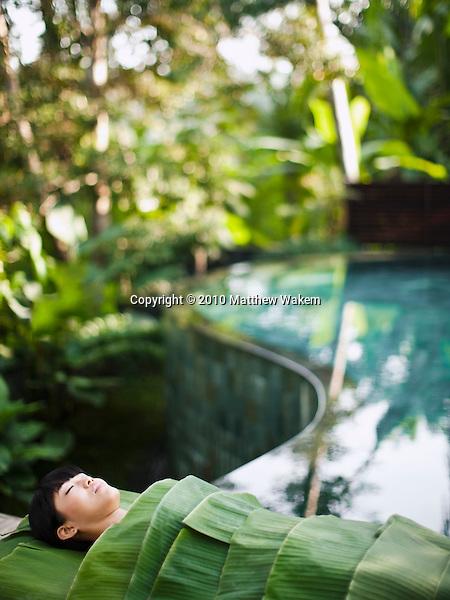Woman wrapped in banana leaves, Kayumanis Spa, Kayumanis Ubud, Bali, Indonesia.