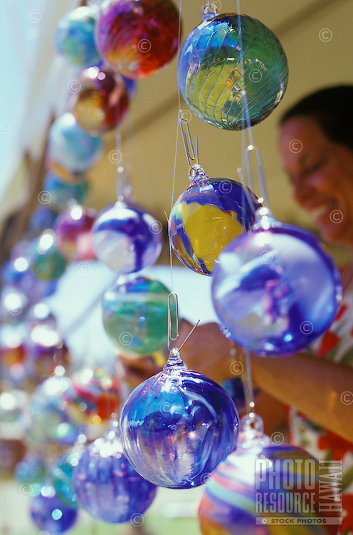 Woman shopping for hand blown glass balls at Haleiwa Art Festival, at Haleiwa Beach Park, Oahu, Hawaii