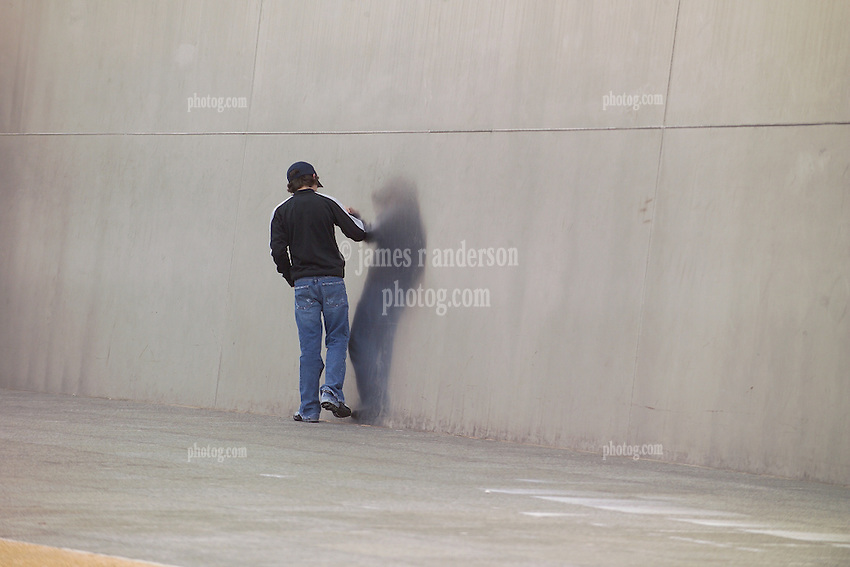 A Teenager Reflecting on the Saint Louis Gateway Arch, Touching the Stainless Steel Surface. Late in the day, a gray afternoon.