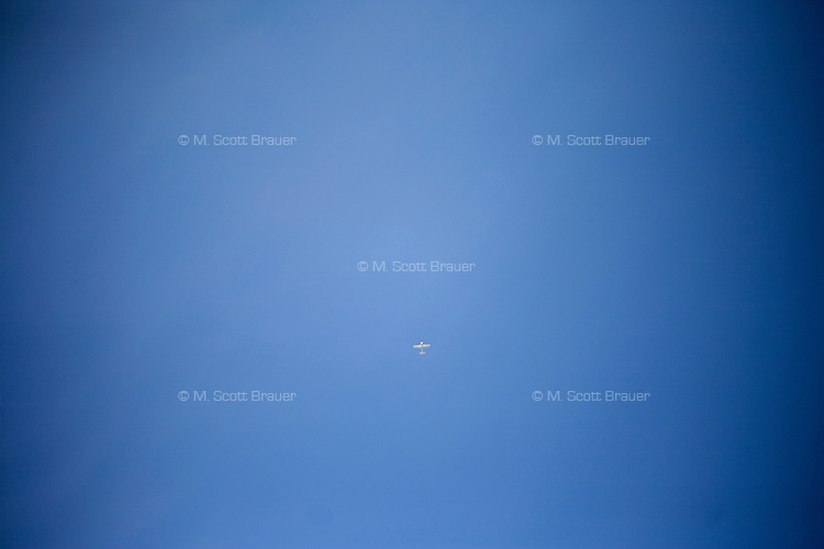 A small plane flies in the sky above Provincetown, Massachusetts, USA.