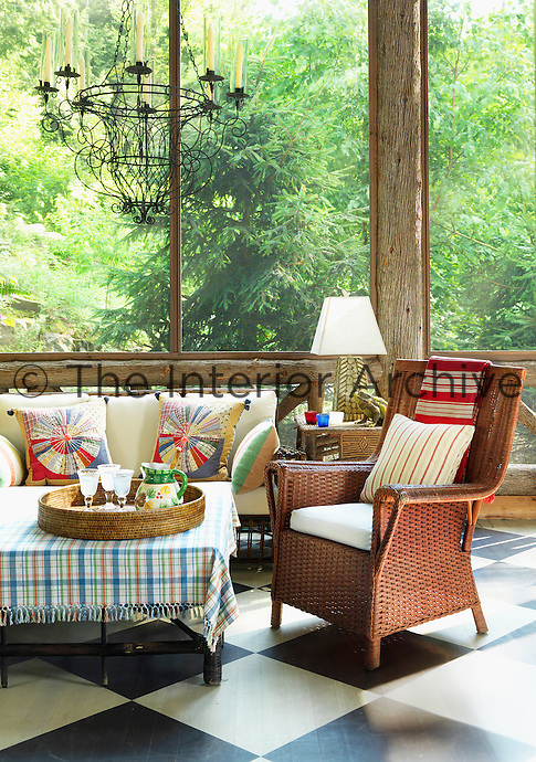 The screened porch has a casual seating area furnished with antique rattan armchairs