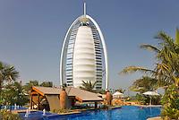 Dubai.  View of Burj al Arab Hotel over executive pool area, pavilions and gardens of Jumeirah Beach Hotel..
