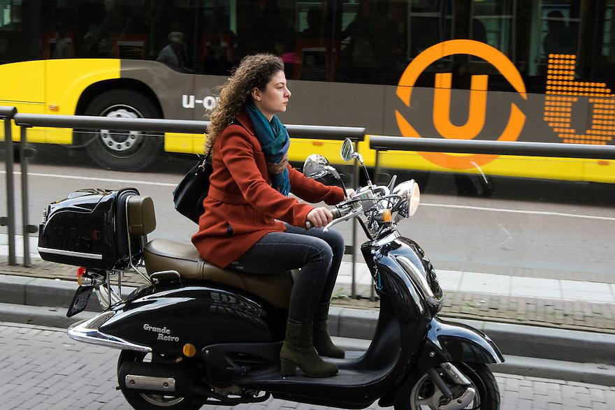 Nederland, Utrecht, 10 okt 2014<br /> Mensen op straat. Meisje op scooter in de stad. Scooters stoten veel schadelijke stoffen uit.<br /> Foto: (c) Michiel Wijnbergh