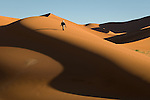 Tourist with photo gear hiking up sand dune in the Sossusvlei region of Namib-Naukluft National Park, Namibia.