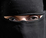 A woman in Gaza City, most of her face covered with a Muslim hijab.