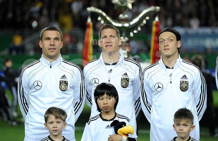 FUSSBALL INTERNATIONAL  EM 2012-Qualifikation  Gruppe A  26.03.2011 Deutschland - Kasachstan Lukas PODOLSKI, Bastian SCHWEINSTEIGER, Mesut OEZIL (v. li., Deutschland)
