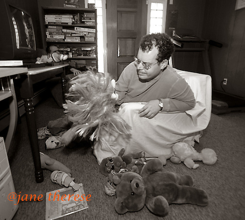 """David Freeman who is autistic and lives in the Soblevitch House in Robbinsville, NJ with Michael Schwallie, plays with his """"companions"""" on Sunday December 12, 2005. Autism is a neurological disorder and is on the rise in America. It is estimated that 1.5 million Americans are afflicted. There is no known cure for autism nor no known origin. Those families afflicted with the disease, have a greater chance of having a child with some form of autism. This includes the siblings offspring as well. photo by jane therese..."""