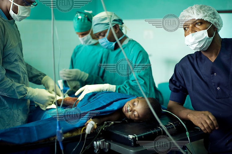 Orthopaedic surgeon, Didier Linard, from Medics without Vacation performs an operation on patient Mukimay's clubfoot at the Hospital du Bon Berger in Kananga.