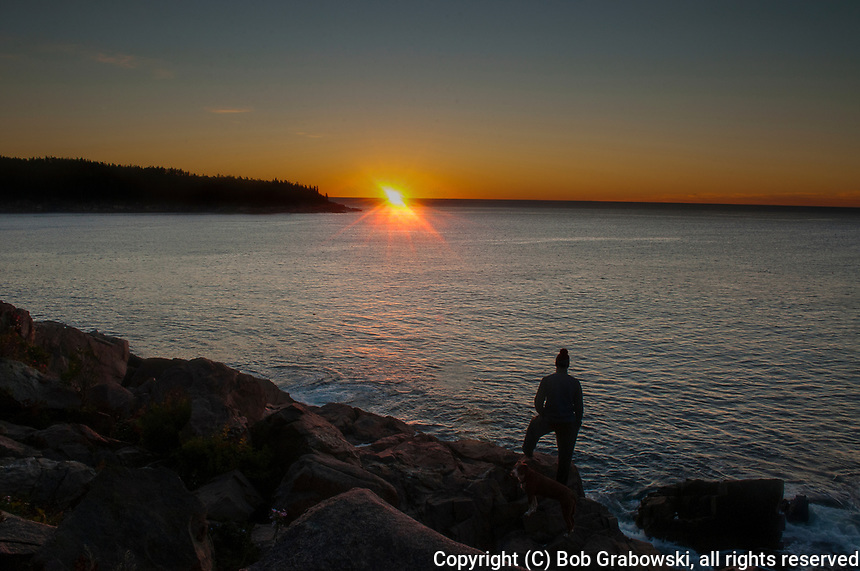 Man watching the sunrise over the Atlantic Ocean at Acadia National Park, Maine