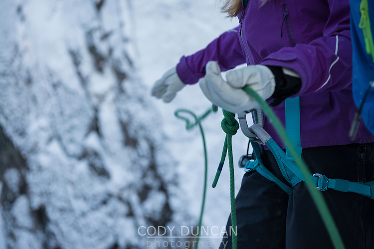Female climber threads rope through hands in winter, Lofoten Islands, Norway