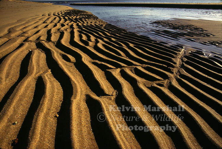 Sunrise on a rippled sandy beach. Cape Runaway - New - Zealand.