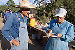 """Aug 9, 2008 -- COLORADO CITY, AZ: JOSEPH JESSOP, 86, patriarch of the Jessop family, polygamists and members of FLDS in Colorado City, AZ, talks to one of his wives during a barbecue at the family home. Colorado City and neighboring town of Hildale, UT, are home to the Fundamentalist Church of Jesus Christ of Latter Day Saints (FLDS) which split from the mainstream Church of Jesus Christ of Latter Day Saints (Mormons) after the Mormons banned plural marriage (polygamy) in 1890 so that Utah could gain statehood into the United States. The FLDS Prophet (leader), Warren Jeffs, has been convicted in Utah of """"rape as an accomplice"""" for arranging the marriage of teenage girl to her cousin and is currently on trial for similar, those less serious, charges in Arizona. After Texas child protection authorities raided the Yearning for Zion Ranch, (the FLDS compound in Eldorado, TX) many members of the FLDS community in Colorado City/Hildale fear either Arizona or Utah authorities could raid their homes in the same way. Older members of the community still remember the Short Creek Raid of 1953 when Arizona authorities using National Guard troops, raided the community, arresting the men and placing women and children in """"protective"""" custody. After two years in foster care, the women and children returned to their homes. After the raid, the FLDS Church eliminated any connection to the """"Short Creek raid"""" by renaming their town Colorado City in Arizona and Hildale in Utah. A member of the Jessop family weeds the community corn plot in Colorado City, AZ. The Jessops are a polygamous family and members of the FLDS. Photo by Jack Kurtz / ZUMA Press"""