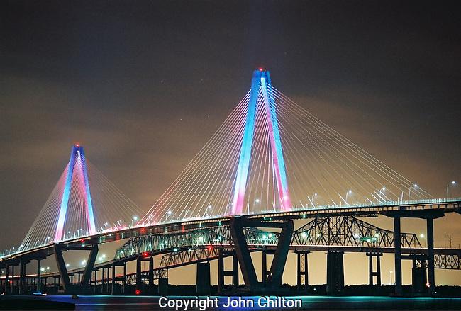 Photo of Ravenel Bridge in Charleston lit in color.