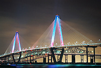 Photo of Ravenel Bridge in Charleston lit in color.