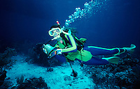 Scuba diver carrying ship?s bell from shipwreck.Belize, Central America.