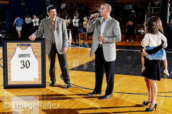 5 January 2008: Orlando Magic point guard Carlos Arroyo (center), with his wife and child, Gabriella (right) nearby, addresses the crowd after being introduced by Florida International Athletic Director Pete Garcia (second from left), as part of the festivities honoring Arroyo by retiring his Florida International jersey number at the half-time of the FIU 69-58 victory over FAU at the Pharmed Arena in Miami, Florida.