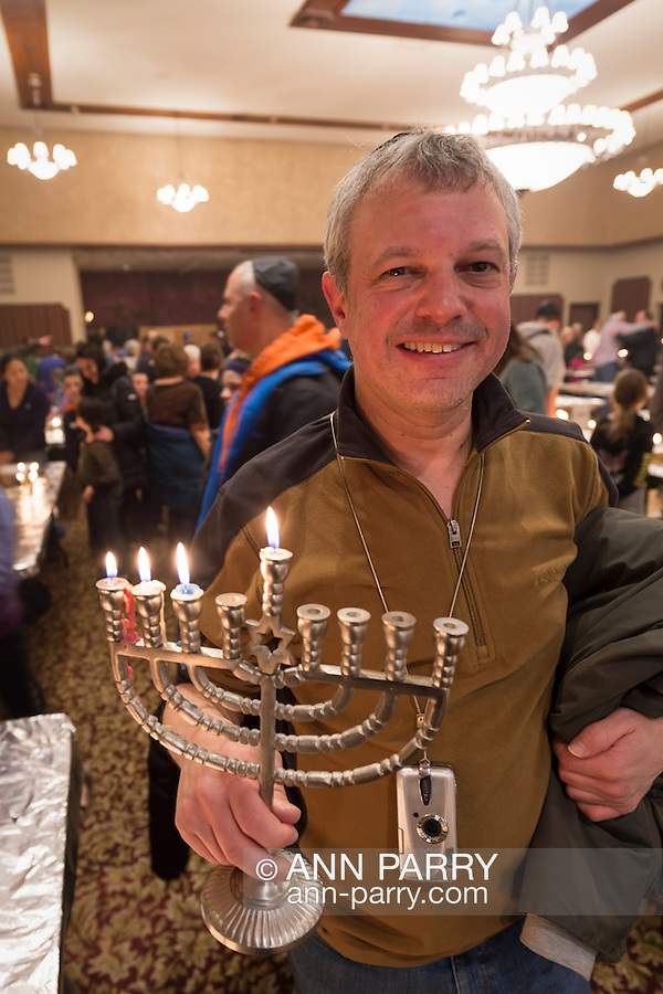 A man carries his menorah with four lit candles when the Merrick Jewish Centre attempts to regain the Guinness World's Record for Most Menorot Lit in One Place at One Time that the congregation held in 2011. On the third night of Hanukkah, the 'Light Up the Night 2 - Bringing the Record Home' event also included a ceremonial candle lighting in the main sanctuary.
