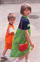 Brother and sister ages 4 and 8 walking hand in hand in brightly colored clothing.  Torun Poland