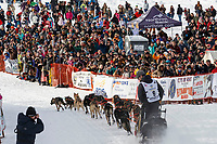 Pete Kaiser and team run down the trail with a crowd cheering during the restart of the 2019 Iditarod race in Willow, Alaska.<br /> <br /> Photo by Jeff Schultz/  (C) 2019  ALL RIGHTS RESERVED