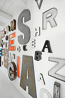 A collection of artwork letters are grouped together and displayed on a wall.