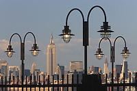 The Empire State Building, Manhattan skyline and Hudson River, seen through the street lamps on the Old Docks in Liberty State Park