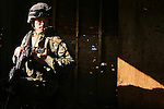 Cpl. Joey McBroom (2nd Platoon, Charlie Co. 1/4 Marines) crouches in the light of an open window during excercises at one of Schofield Army Barracks' urban training facilities where the 11th MEU's infantry companies and attached units took part in two days of live fire training while en route to a scheduled seven month deployment in Iraq.<br />