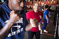 NWA Democrat-Gazette/CHARLIE KAIJO Michelle Wilkins of Fayetteville (center) listens to instructions on boxing fundamentals from boxing coach Bernard Oliver (left) during a boxing class, Monday, June 11, 2018 at  Straightright Boxing and Fitness in Springdale.<br />