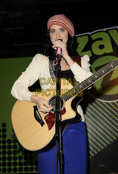 KATY PERRY.A live performance & signing session at Zavvi, Oxford Street, London, England.November 11th, 2008.half length katie concert stage gig music  white cardigan hat pink heart belt singing striped stripes blue skirt guitar .CAP/CAN.©Can Nguyen/Capital Pictures.