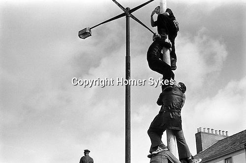 Egremont Crabapple Fair, Cumbria. England 1975. Climbing the 40 foot tall greasy pole. The prize is £1-00 for the first to the top.