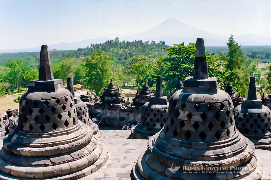 Java, Central Java, Borobodur.  Borobudur is a 9th-century Buddhist monument near Magelang, Central Java. Stupas with the mount Merapi volcano in the background.