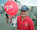 Oscar Mabini holds a balloon celebrating international solidarity with survivors in Tacloban, a city in the Philippines province of Leyte that was hit hard by Typhoon Haiyan in November 2013. The storm was known locally as Yolanda. Mabini also holds a photo of his daughter Cristina, who along with two of her children perished in the storm.