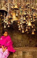 A lady resting under temple bells, India