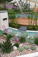 Waterfall in modern water garden with raised beds, circular wooden deck, white walls, perennials, flowers, for a clean classic landscaping look using succulent plants for water-wise planting