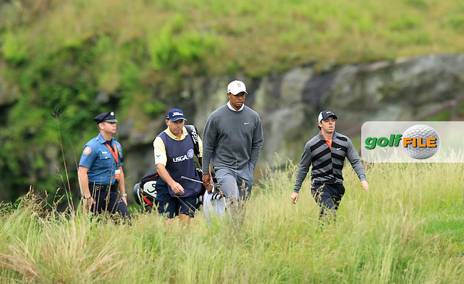 Tiger Woods (USA) and Rory McIlroy (NIR) walk through the quarry to the 17th green during Friday's rain delayed Round 1 of the 113th U.S.Open National Championship held at Merion Golf Club, Ardmore, Philadelphia, Pennsylvania. <br /> 14th June 2013<br /> (Picture: Eoin Clarke www.golffile.ie)