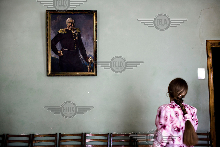 A girl looks at and pays her repsects to a painting of a famous Cossack Warrior hanging on a wall at the Pyatigorsk Cossack Academy.