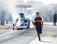 Oct 14, 2017; Ennis, TX, USA; Gary Pritchett , crew member for NHRA top fuel driver Steve Torrence runs alongside the dragster during a burnout in qualifying for the Fall Nationals at the Texas Motorplex. Mandatory Credit: Mark J. Rebilas-USA TODAY Sports
