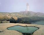 Halifax County, Nova Scotia, Canada: Peggys Point Lighthouse at Peggys Cove in thick fog, at the entrance to St. Margarets Bay
