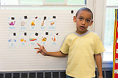 MR / Schenectady, NY. Zoller Elementary School (urban public school). Kindergarten classroom. Student (boy, 6, African American /  Puerto-Rican American) points to vocabulary word card during Spanish lesson for bilingual students. MR: Car38. ID: AM-gKw. © Ellen B. Senisi.