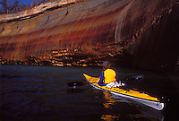 A sea kayaker examines mineral stains on cliffs at Pictured Rocks National Lakeshore near Munising, Mich.