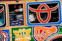 A Haitian woman looks out of the window of the tap-tap bus in the downtown of Port-au-Prince, Haiti, 24 July 2008. Tap-tap vehicles serve as public transportation in Haiti. They are private, operate over fixed routes, departing only when full. Tap-taps are decorated with bright and shiny colors and with a lot of fancy designed elements. There are scenes from the Bible, Christian slogans, TV stars or famous football players often painted on a tap-tap body. Tap-tap name comes from sound of taps on the metal bus body signifying a passenger's request to be dropped off.
