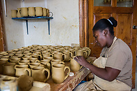 Haiti, Port-au-Prince. Artisan business, Papillon. Produce ceramics, jewelry, t-shirts. Over 300 women on payroll (men work her as well), making about $15 a day. Woman working in ceramics.