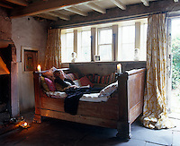Celia Lyttelton photographed relaxing on the daybed in the living room of her restored 17th-century weaver's cottage on Wuthering Heights, Yorkshire