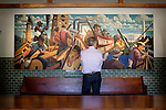 """A guest looks at a commissioned mural of the movie """"Tucker: The Man and His Dream,"""" which is on loan by the movie producer George Lucas for the winery, at Francis Ford Coppola Winery, in Geyserville, Ca., on Saturday, July 31, 2010."""