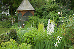 A dovecote adds to the Victorian feel of the Sissinghurst-style white garden behind the late 19th c. farmhouse on this property about one hour north of Seattle in the Skagit Valley, that also includes white delphiniums, white peonies, white climbing and shrub roses, white irises, and bleeding heart, among others. Garden design by Toni Christianson, Christianson's Nursery