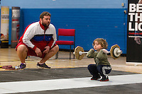 23 FEB 2014 - SMETHWICK, GBR - A young weightlifting fan, watched by his father, practices during a break at the 2014 English Weightlifting Championships at the Harry Mitchell Leisure Centre in Smethwick, Great Britain (PHOTO COPYRIGHT &copy; 2014 NIGEL FARROW, ALL RIGHTS RESERVED)<br /> ==========================================<br /> USE WITH CARE - IMAGE FEATURES A CHILD UNDER  16 YEARS OLD<br /> ==========================================