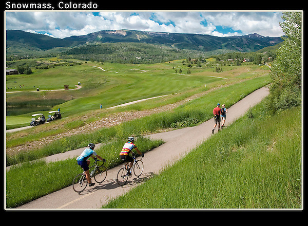 Cyclists and couple walking along the Snowmass Village Golf Course, Aspen, Colorado, USA